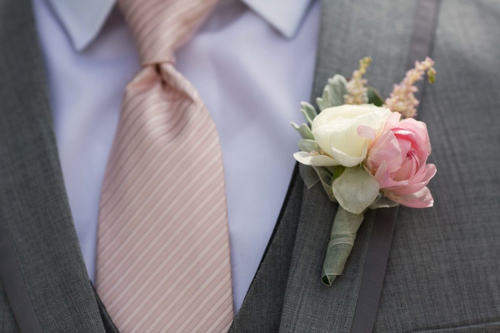 Close look at groom's blush tie and boutonniere