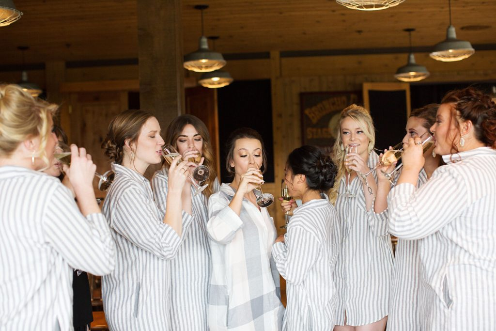 Bridal party drinking champagne while getting ready