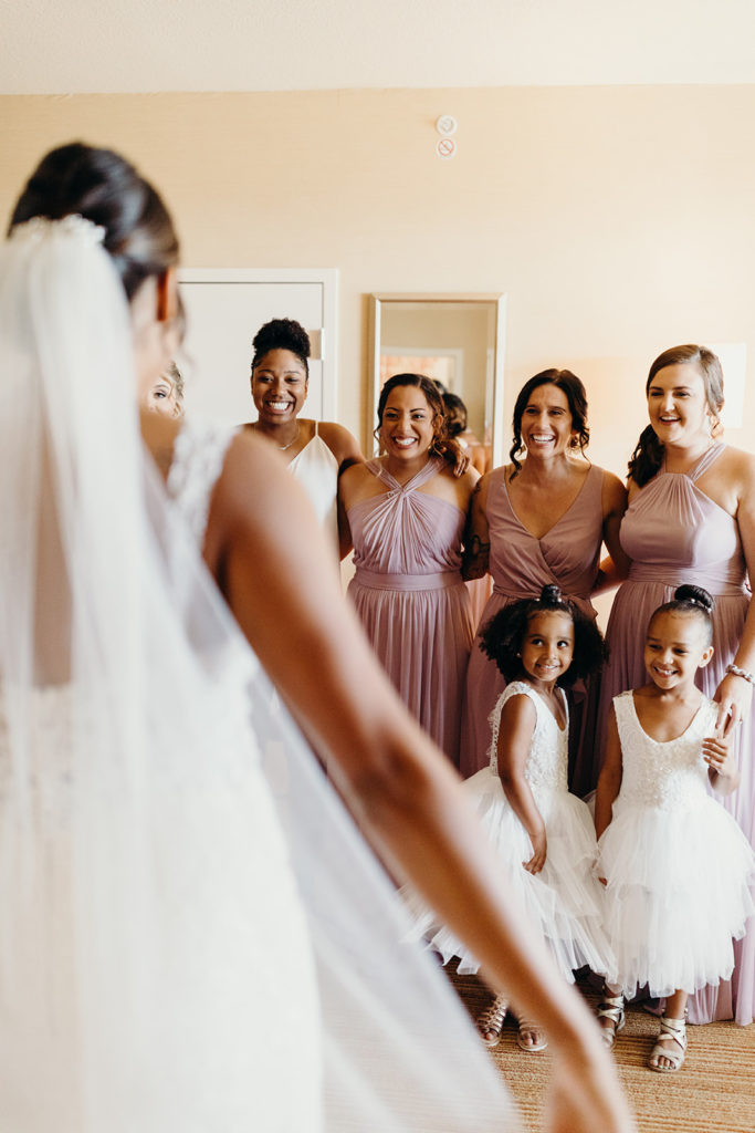 Bride reveals dress as bridesmaids in mauve dresses and flower girls look on with big smiles