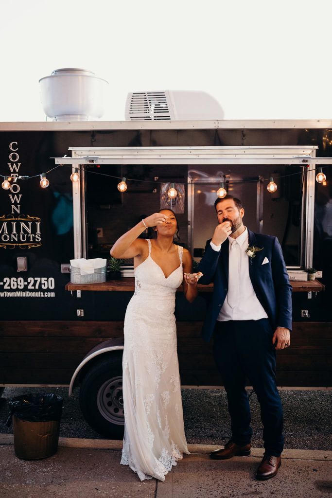 Bride and groom take first bite of donut at Cowtown Mini Donuts truck