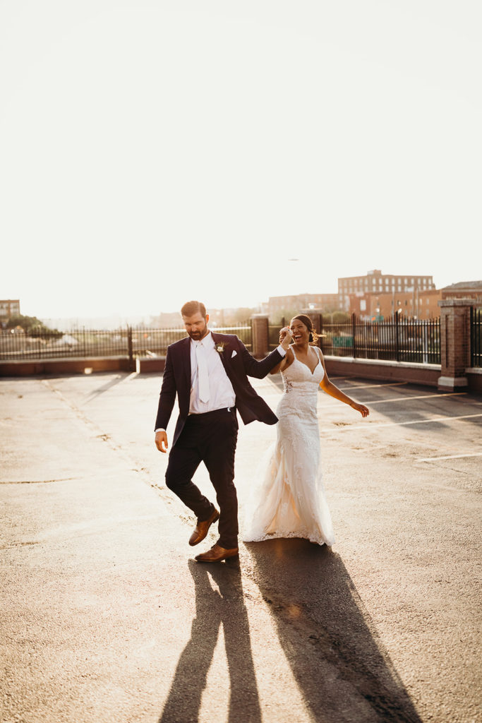 Bride and groom walk hand in hand through downtown Kansas City parking lot at golden hour