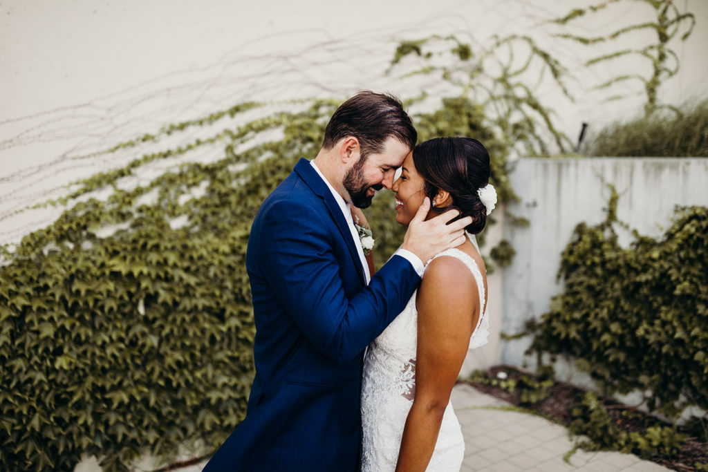 Bride and groom touch foreheads as they pose in front of greenery wall at Kauffman Center