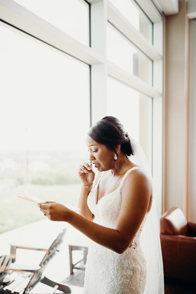 Bride in fitted lace dress tears up as she reads letter from soon-to-be husband
