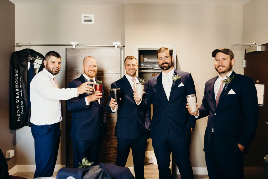 Groomsmen in navy suits hold up Yeti mugs as they get ready in hotel room