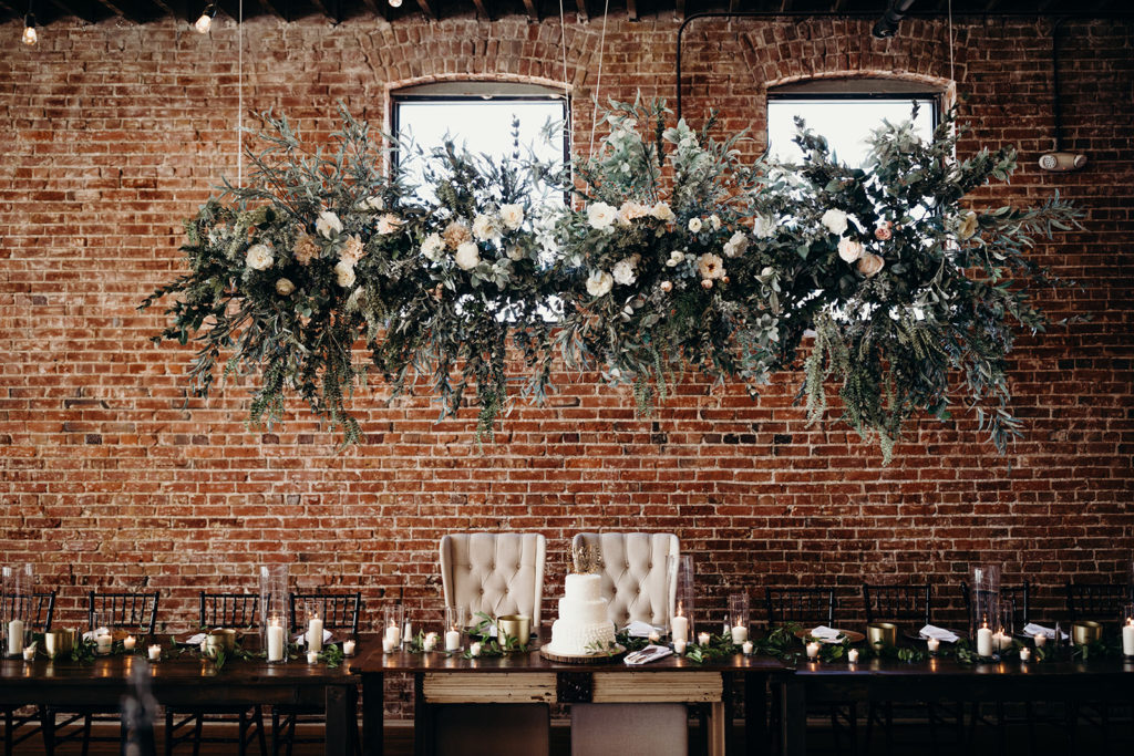 Head table at Magnolia Venue & Urban garden with exposed brick backdrop and hanging floral installation above
