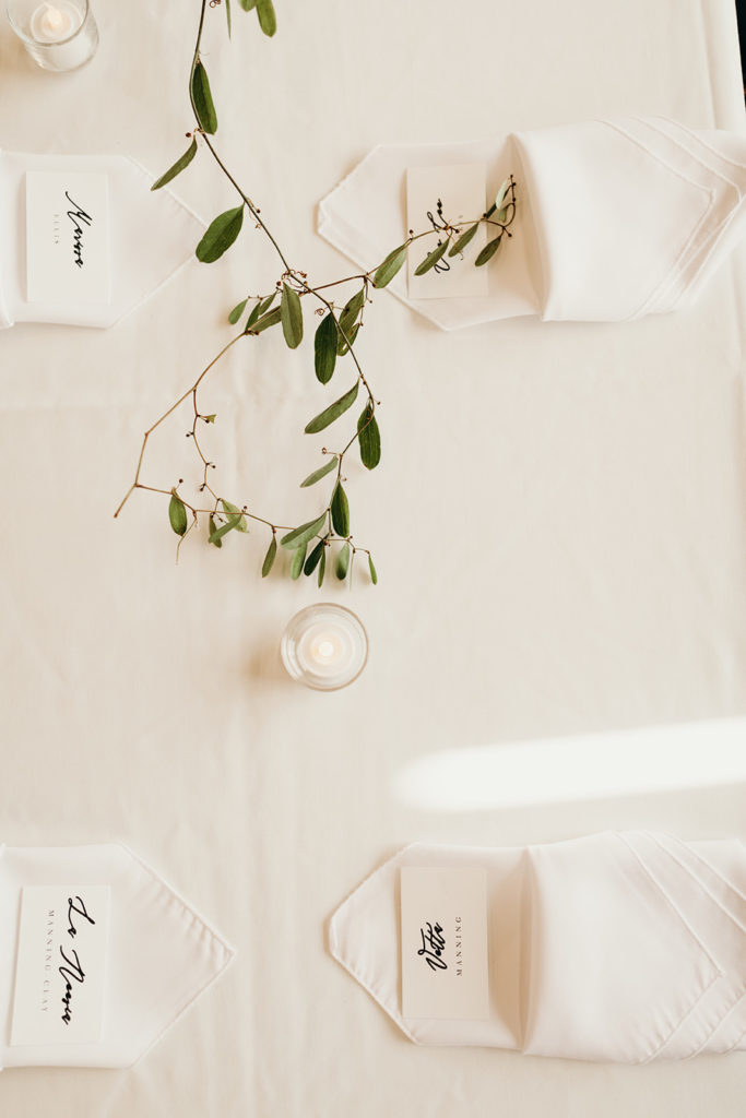 Minimalist wedding table setting at Magnolia Venue & Urban Garden with white table linen, white napkin, votive candle and simple greenery garland