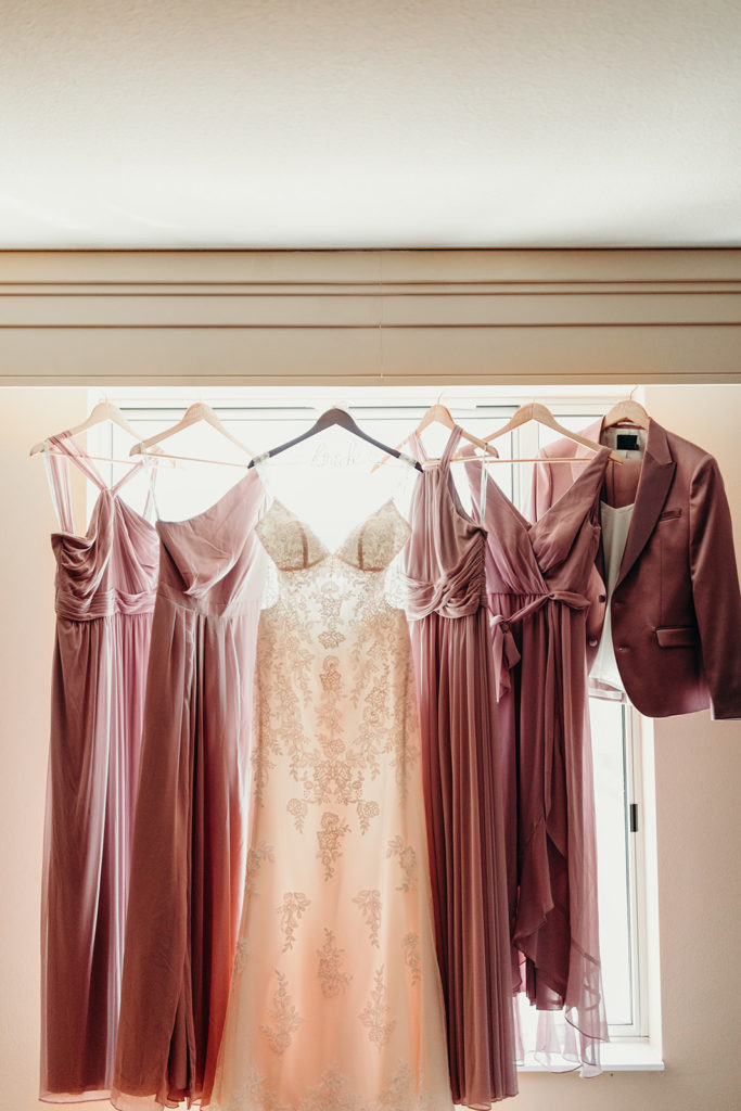 Mauve bridesmaid dresses hanging in window with ivory lace wedding dress