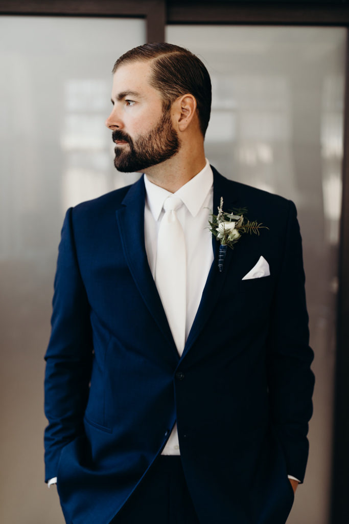 Bearded looks to side in navy suit with white tie and white pocket square