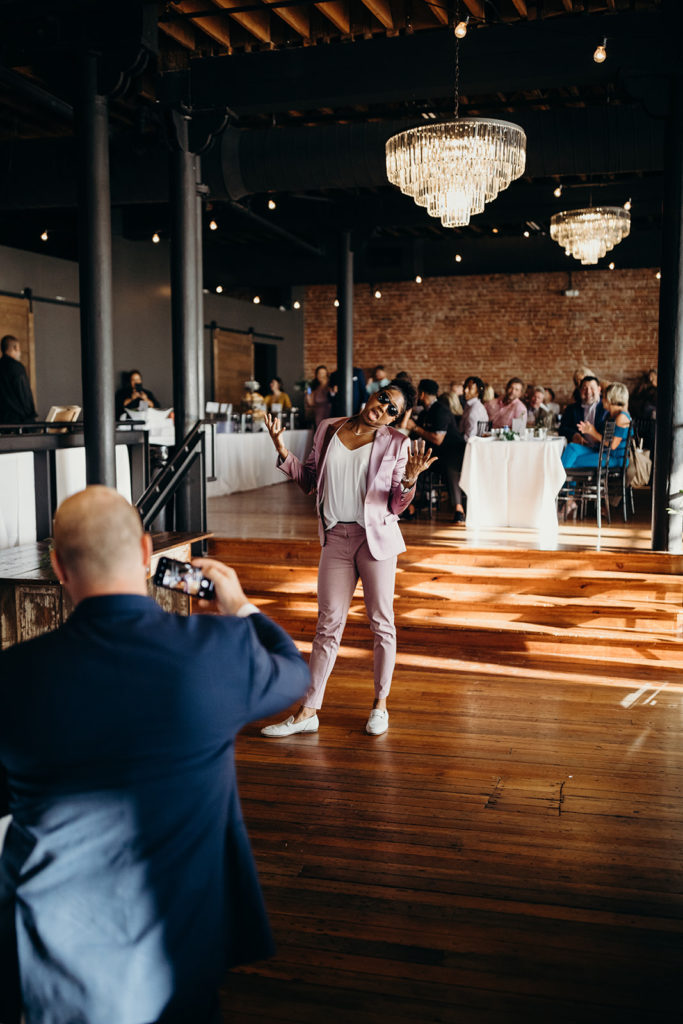 Maid of honor in mauve non-dress outfit poses as she's introduced at Magnolia Venue wedding reception
