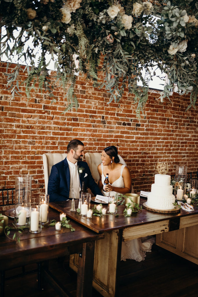 Bride and groom smile at each other at romantic head table at Magnolia Venue & Urban Garden